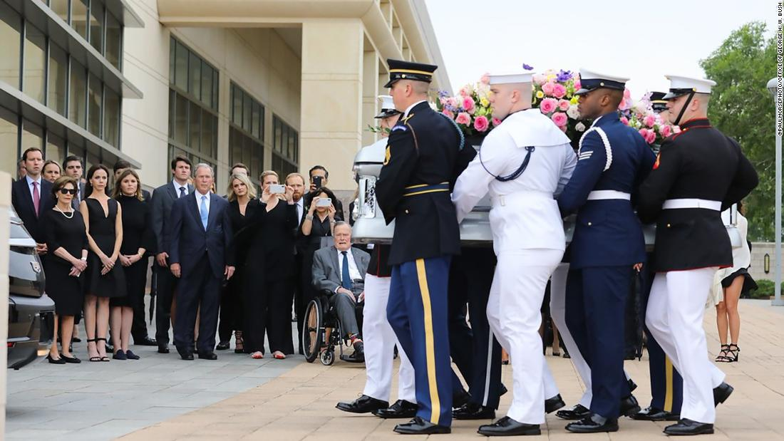 The casket of the late first lady Barbara Bush passes as members of her family, including former presidents George W. Bush and George H.W. Bush, look on.