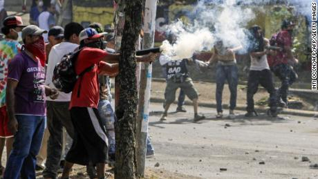 TOPSHOT - Students clash with riot police agents close to Nicaragua's Technical College during protests against government's reforms in the Institute of Social Security (INSS) in Managua on April 21, 2018. - Violent protests against a proposed change to Nicaragua's pension system have left at least 10 people dead over two days, the government said Friday. In the biggest protests in President Daniel Ortega's 11 years in office in this poor Central American country, people are angry over the plan because workers and employers would have to chip in more toward the retirement system. (Photo by INTI OCON / AFP)        (Photo credit should read INTI OCON/AFP/Getty Images)
