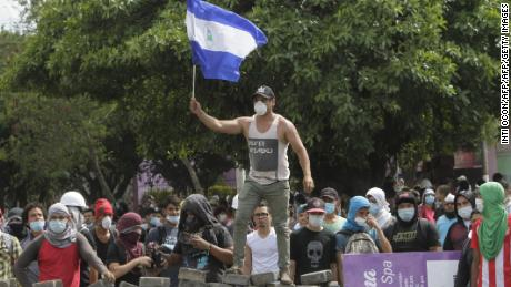 A student waves the Nicaraguan national flag over a barricade close Nicaragua's Technical College during a protest against government's reforms in the Institute of Social Security (INSS) in Managua on April 21, 2018. - A protester and a policeman were killed in the Nicaraguan capital Managua after demonstrations over pension reform turned violent Thursday night, officials said. The deaths came after protests by both opponents and supporters of a new law, which increases employer and employee contributions while reducing the overall amount of pensions by five percent, rocked the capital for a second day. (Photo by INTI OCON / AFP)        (Photo credit should read INTI OCON/AFP/Getty Images)