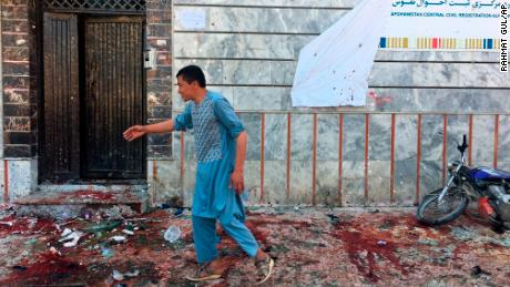 An Afghan man walks outside a voter registration center,  which was attacked by a suicide bomber in Kabul, Sunday, April 22, 2018. (AP Photo/ Rahmat Gul)