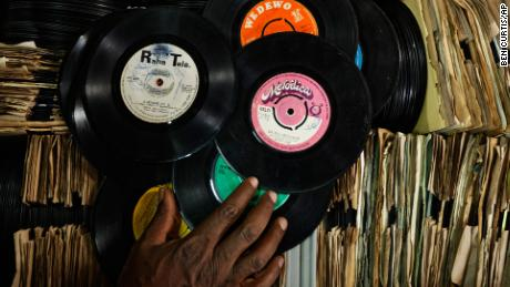 "James ""Jimmy"" Rugami sorts through records inside his vinyl records stall in Kenyatta Market."