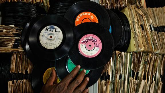 "James ""Jimmy"" Rugami sorts through records inside his vinyl records stall in Kenyatta Market."