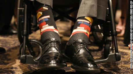This Saturday, April 21, 2018, photo provided by the Office of former U.S. President George H.W. Bush shows Bush's socks during the funeral service for his wife, Barbara Bush, in Houston.  Barbara Bush was known for bringing awareness to AIDS patients and for her work promoting literacy, which her husband subtly honored Saturday by wearing socks printed with blue, red and yellow books. (Paul Morse/Courtesy of Office of George H.W. Bush via AP)