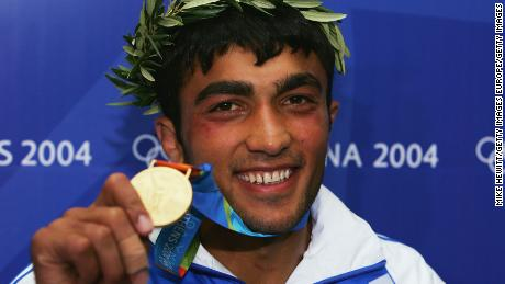 A smiling Iliadis holds the gold medal at the Athens 2004 Olympic Games.