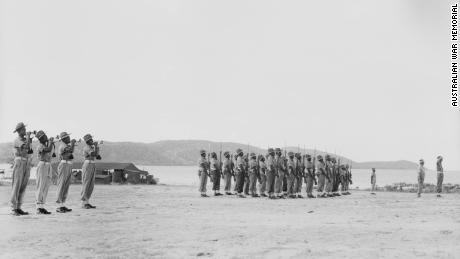 Troops of the Torres Strait Light Infantry Battalion present arms during the lowering of the colors on October 10, 1945.