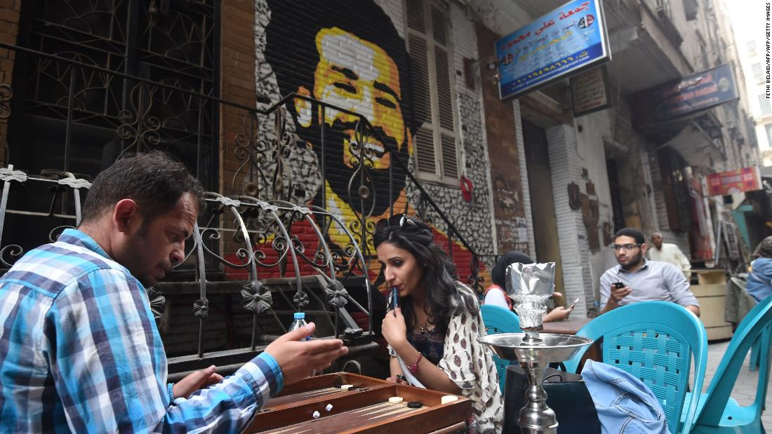 Egyptians gather at a café near a mural of Salah.