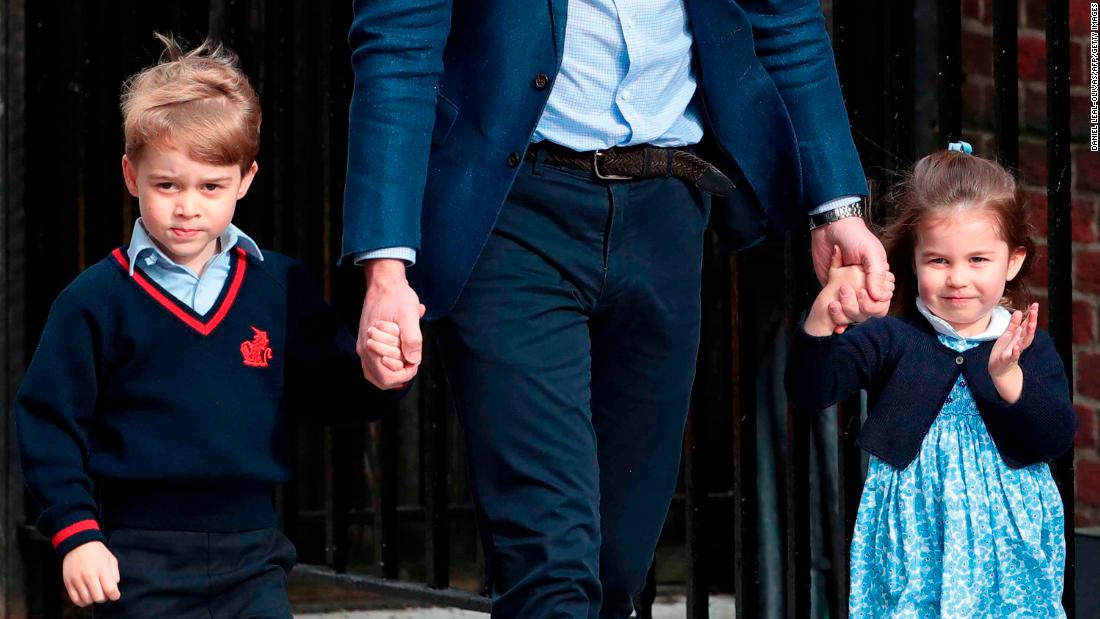 Prince William holds the hands of his other two children, Prince George and Princess Charlotte, as they visit the hospital to meet their new brother.