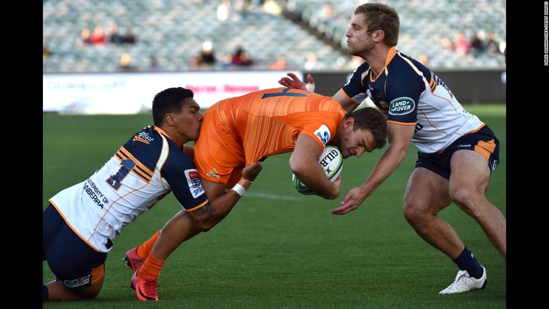 Emiliano Boffelli, a rugby player for the Jaguares, is tackled by the Brumbies' Chance Peni, left, and Kyle Godwin during a Super Rugby match in Canberra, Australia, on Sunday, April 22.