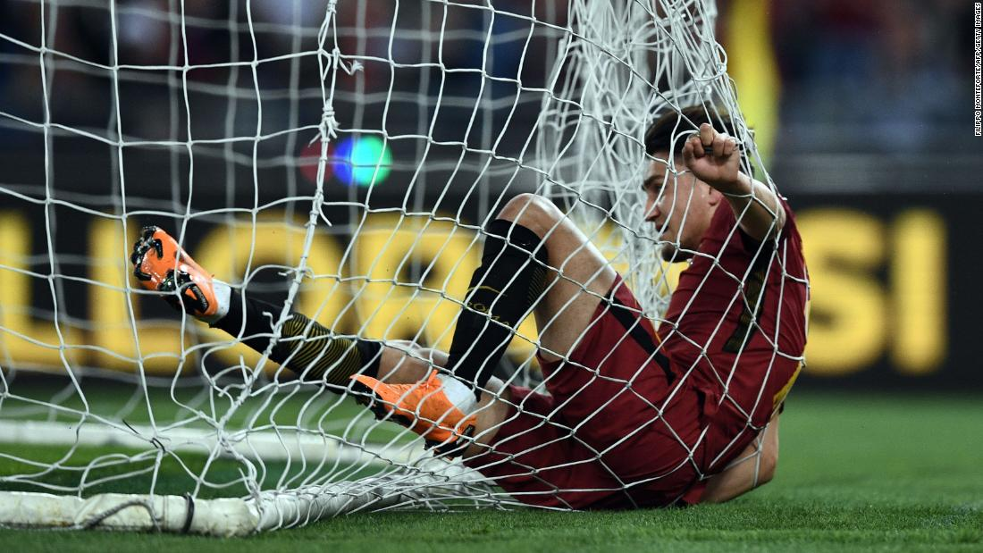 Roma's Cengiz Under falls into the net after scoring a goal against Genoa during an Italian league match on Wednesday, April 18. Roma won the match 2-1.