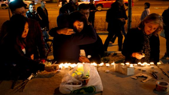 TORONTO, ON - APRIL 23: People embrace as they lay candles and leave messages at a memorial for victims of a crash on Yonge St. at Finch Ave., after a van plowed into pedestrians on April 23, 2018 in Toronto, Canada. A suspect identified as Alek Minassian, 25, is in custody after a driver in a white rental van collided with multiple pedestrians killing nine and injuring at least 16. (Photo by Cole Burston/Getty Images)