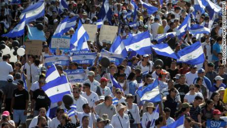 "People, many who demand Nicaraguan President Daniel Ortega and his wife, Vice-President Rosario Murillo, to step down, take part in the ""Walk for Peace and Dialogue"" in Managua on April 23, 2018. - Ortega was under pressure from widespread street unrest on Monday despite backing down on a contentious pension reform plan that triggered days of violence in which at least 27 people have been killed. (Photo by Inti OCON / AFP)        (Photo credit should read INTI OCON/AFP/Getty Images)"