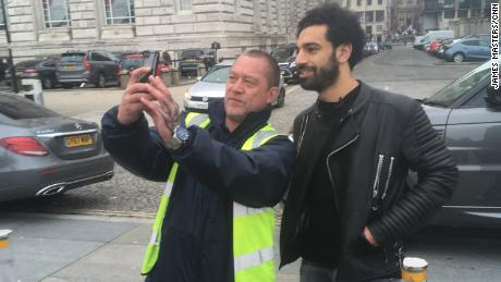 Salah pauses for a selfie with a fan while walking by the River Mersey.