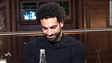 Salah watches a video message from his first coach back in Egypt while waiting for dinner.