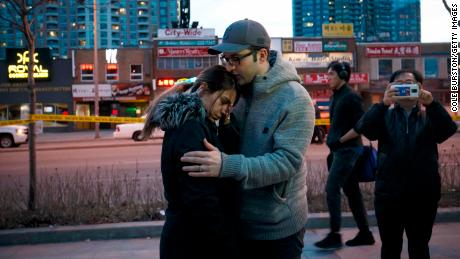 TORONTO, ON - APRIL 23: People embrace at the scene of a memorial for victims of a crash at Yonge St. at Finch Ave., after a van plowed into pedestrians on April 23, 2018 in Toronto, Canada. A suspect identified as Alek Minassian, 25, is in custody after a driver in a white rental van collided with multiple pedestrians killing nine and injuring at least 16. (Photo by Cole Burston/Getty Images)
