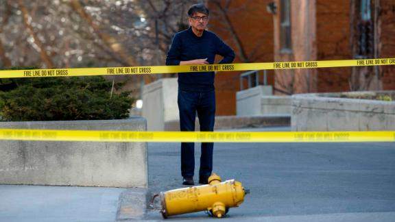 A bystander looks on near a dislodged fire hydrant at the scene.