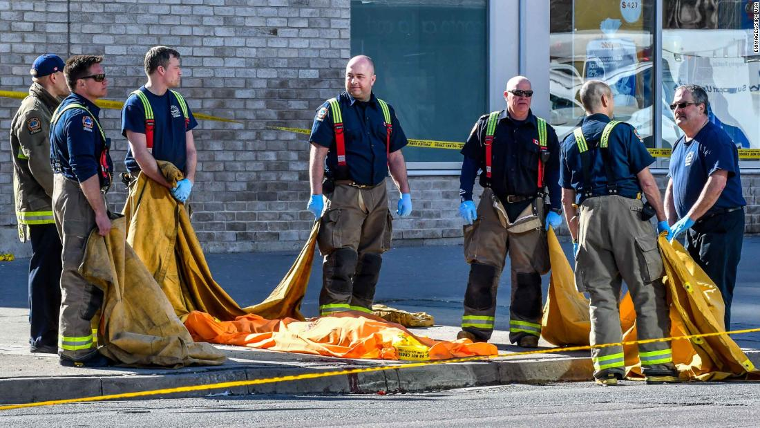 Emergency workers stand around the body of a victim.