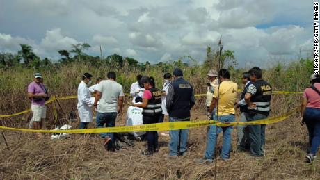 Policemen and locals unearth the body of a Canadian man who authorities say was lynched by a mob in remote Peru.