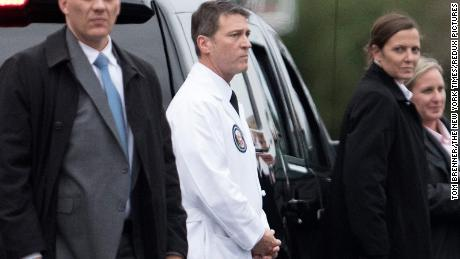 FILE-- Dr. Ronny Jackson, the White House physician, looks on as President Donald Trump boards Marine One en route to Joint Base Andrews, at the Walter Reed National Military Medical Center in Bethesda, Md., Jan. 12, 2018. After weeks of uncertainty atop the Department of Veterans Affairs, President Trump on Wednesday said he plans to replace its secretary, David Shulkin, with Jackson, the president's personal physician who is a rear admiral in the Navy. (Tom Brenner/The New York Times)