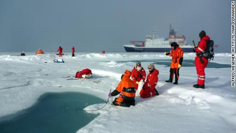 Researchers at melt pond on arctic sea ice