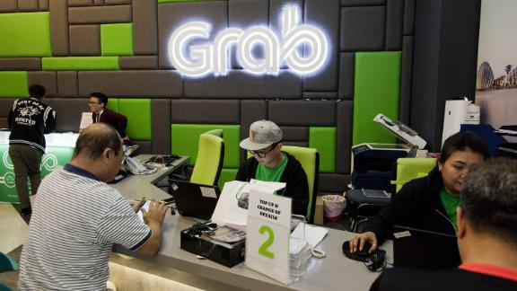 Employees attend to customers in the GrabCar division of Grab's office in Midview City in Singapore, on Wednesday, Oct. 19, 2016. Grab is riding a Southeast Asian ride-hailing arena with some 620 million people, forecast to grow more than five times to $13 billion by 2025. Photographer: Ore Huiying/Bloomberg via Getty Images