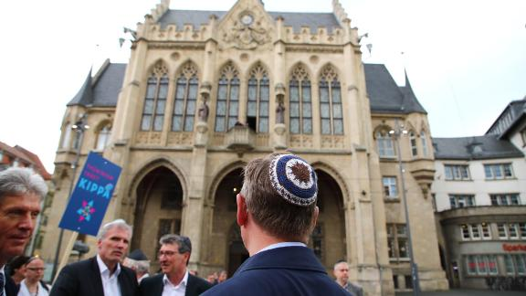 Thuringia's State Premier Bodo Ramelow (C) wears a kippa during a rally in Erfurt.