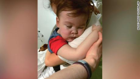 In this April 23, 2018 handout photo provided by Alfies Army Official, brain-damaged toddler Alfie Evans cuddles his mother Kate James at Alder Hey Hospital, Liverpool, England. The father of a terminally ill British toddler said the child is surviving after being taken off life support, surprising doctors who had argued he should be allowed to die. Tom Evans said his 23-month-old son, Alfie, survived for six hours with no assistance, and that doctors are now providing oxygen and hydration. (Alfies Army Official via AP)