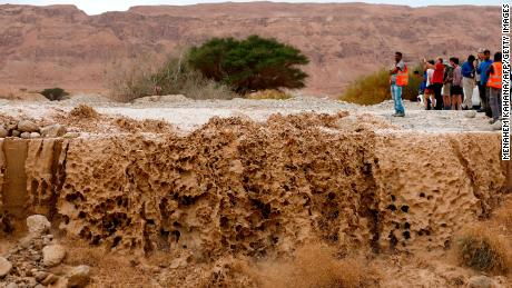 A crowd watches as floodwaters rush through a valley Thursday in the Judean Desert.