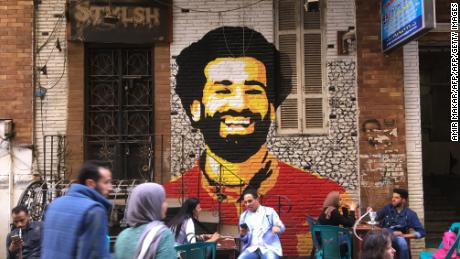 A picture taken on April 4, 2018 shows people sitting at a cafe in downtown Cairo with a mural depicting Liverpool FC's Egyptian striker Mohamed Salah painted in the background. / AFP PHOTO / Amir MAKAR        (Photo credit should read AMIR MAKAR/AFP/Getty Images)