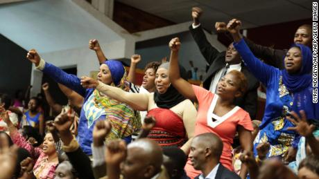 Rwandan people react during the Constitution amendment debate at the parliament in Kigali on July 14, 2015. Rwandan lawmakers voted today in support of a constitutional change to allow strongman Paul Kagame a third term in power as president, backing a petition signed by millions of citizens.  AFP PHOTO / CYRIL NDEGEYA        (Photo credit should read Cyril Ndegeya/AFP/Getty Images)