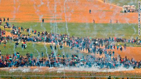 A picture taken on March 30, 2018 from the southern Israeli kibbutz of Nahal Oz across the border from the Gaza strip shows tear gas grenades falling during a Palestinian tent city protest commemorating Land Day, with Israeli soldiers seen below in the foreground. Land Day marks the killing of six Arab Israelis during 1976 demonstrations against Israeli confiscations of Arab land. / AFP PHOTO / Jack GUEZ        (Photo credit should read JACK GUEZ/AFP/Getty Images)