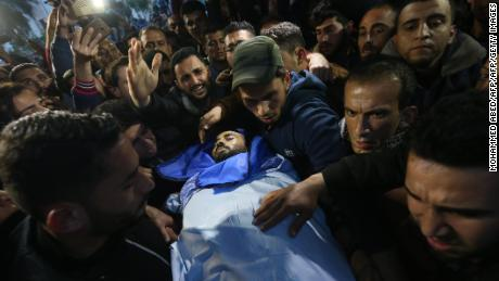 Mourners carry the body of journalist Ahmad Abu Hussein in Beit Lahia on Wednesday.