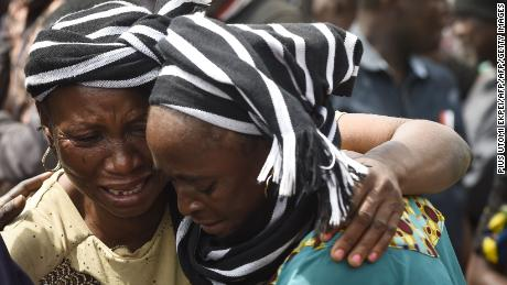 A woman cries while trying to console a woman who lost her husband during the funeral service for people killed during clashes between cattle herders and farmers, on January 11, 2018, in Ibrahim Babangida Square in the Benue state capital Makurdi. Violence between the mainly Muslim Fulani herdsmen and Christian farmers has claimed thousands of lives across Nigeria's central states over the past few decades. The conflict is being driven by an increasing need for resources -- primarily land and water -- and is often exacerbated by ethnic and sectarian grievances.   / AFP PHOTO / PIUS UTOMI EKPEI        (Photo credit should read PIUS UTOMI EKPEI/AFP/Getty Images)