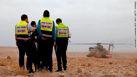 Rescue service personnel stand by Thursday during a search for youths in southern Israel.