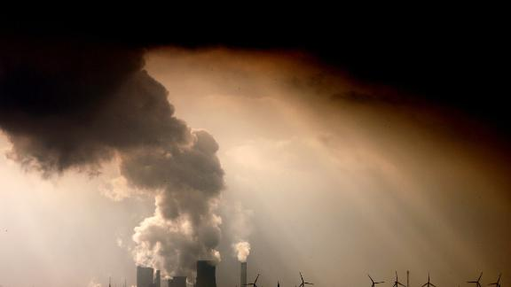 """TOPSHOT - Picture taken on September 30, 2009 shows smoke and vapor rising from the cooling towers and chimneys of the lignite-fired power plant Niederaussem run by German energy supplier RWE near Bergheim, western Germany. Peruvian farmer Saul Luciano Lliuya accuses German energy giant RWE of contributing to climate change that is threatening his home and livelihood in the Andes. A lower court in the western city of Essen where RWE is based dismissed the initial lawsuit in December 2016, ruling that Luciano had failed to demonstrate a direct link between the German utility and the flood risk. Luciano, who is also a mountain guide, is now hoping the higher court in the city of Hamm will side with him in what German media have likened to a """"David versus Goliath"""" battle. The appeal hearing started on November 13, 2017. / AFP PHOTO / dpa / Oliver Berg / Germany OUT        (Photo credit should read OLIVER BERG/AFP/Getty Images)"""