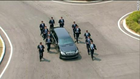 A black vehicles surrounded by security guards shuttles Kim Jong Un back to the North Korea side of the DMZ for lunch .