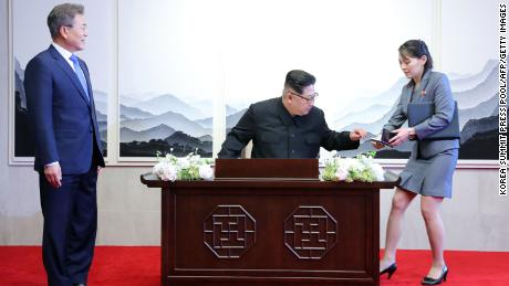 North Korea's leader Kim Jong Un (C) prepares to sign the guest book next to his sister Kim Yo Jong during the Inter-Korean summit with South Korea's President Moon Jae-in (L) at the Peace House building on the southern side of the truce village of Panmunjom, April 27, 2018.