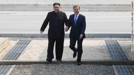 TOPSHOT - North Korea's leader Kim Jong Un (L) steps with South Korea's President Moon Jae-in (R) across the Military Demarcation Line that divides their countries ahead of their meeting at the official summit Peace House building at Panmunjom on April 27, 2018. - North Korean leader Kim Jong Un and the South's President Moon Jae-in sat down to a historic summit Friday after shaking hands over the Military Demarcation Line that divides their countries in a gesture laden with symbolism. (Photo by Korea Summit Press Pool / Korea Summit Press Pool / AFP)        (Photo credit should read KOREA SUMMIT PRESS POOL/AFP/Getty Images)