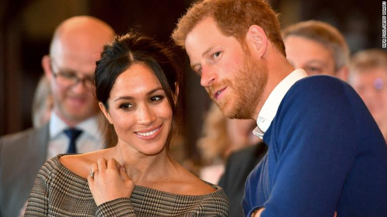 Prince Harry whispers to Meghan Markle as they watch a dance performance by Jukebox Collective in the banqueting hall during a visit to Cardiff Castle on January 18, 2018 in Cardiff, Wales.