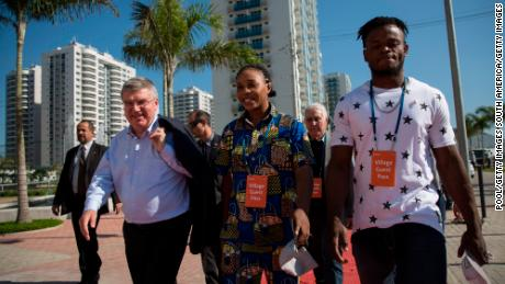 RIO DE JANEIRO, BRAZIL - JUNE 15:  IOC President Thomas Bach (L) walks with refugees and judo athletes from the Democratic Republic of Congo Yolande Mabika (C) and Popole Misenga as they visit an apartment at the Olympic Village on June 15, 2016 in Rio de Janeiro, Brazil.  (Photo by Felipe Dana-Pool/Getty Images)