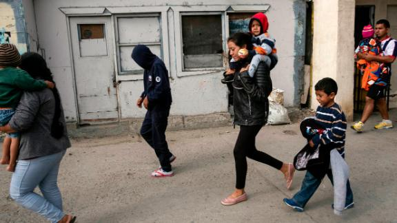 Gabriela Hernandez carries  Jonathan, 2, while Omar, 6, walks beside her before they presented themselves to US border officials.