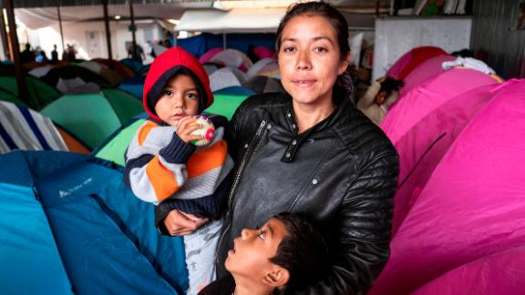 "Gabriela Hernandez and her children Jhonnathan and Omar, Central American migrants traveling in the ""Migrant Via Crucis"" caravan stand for a portrait outside near their tent at Juventud 2000 shelter   in Tijuana, Baja California state, Mexico, on April 27, 2018."