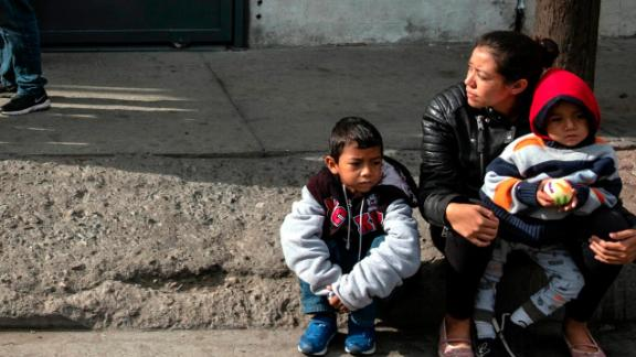 "Gabriela Hernandez and her children Jhonnathan and Omar, Central American migrants traveling in the ""Migrant Via Crucis"" caravan sit outside Juventud 2000 shelter   in Tijuana, Baja California state, Mexico, on April 27, 2018."
