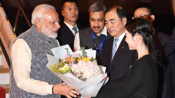 Indian Prime Minister Narendra Modi, left, receives a bunch of flowers after arriving in Wuhan in China's central Hubei province on April 27, 2018.