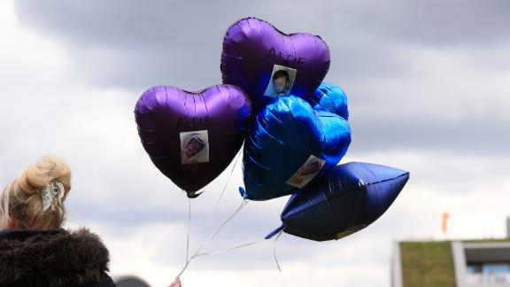 A woman holds balloons with photos of Alfie Evans on Saturday.