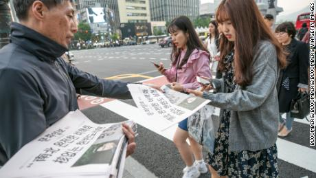 A commuter in Seoul picks up a copy of an extra edition of the Munhwa Ilbo newspaper featuring an image of Moon and Kim on Friday.