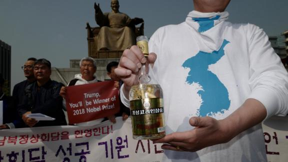 A pro-unification activist in Seoul holds a bottle of ginseng wine from the North Korean city of Kaesong on Friday.