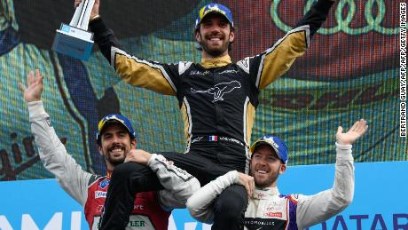 France's Jean-Eric Vergne is hoisted aloft by runner-up Lucas di Grassi (far left) and Britain's Sam Bird after winning the Formula E race in Paris.