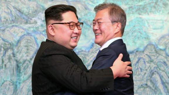 """TOPSHOT - North Korea's leader Kim Jong Un (L) and South Korea's President Moon Jae-in (R) hug during a signing ceremony near the end of their historic summit at the truce village of Panmunjom on April 27, 2018. - The leaders of the two Koreas held a landmark summit on April 27 after a highly symbolic handshake over the Military Demarcation Line that divides their countries, with the North's Kim Jong Un declaring they were at the """"threshold of a new history"""". (Photo by Korea Summit Press Pool / Korea Summit Press Pool / AFP)        (Photo credit should read KOREA SUMMIT PRESS POOL/AFP/Getty Images)"""