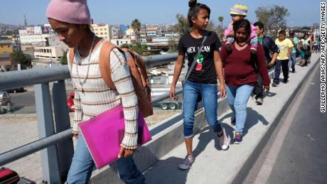 "Central American migrants travelling in the ""Migrant Via Crucis"" caravan walk to their legal counselling meeting in Tijuana, Baja California state, Mexico, on April 28, 2018. - The US has threatened to arrest around 100 Central American migrants if they try to sneak in from the US-Mexico border where they have gathered, prompting President Donald Trump to order troop reinforcements on the frontier. (Photo by GUILLERMO ARIAS / AFP)        (Photo credit should read GUILLERMO ARIAS/AFP/Getty Images)"