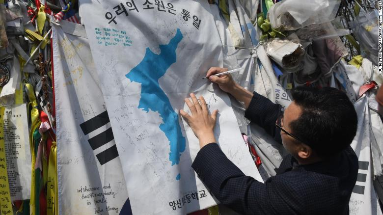 "A man writes an inscription calling for peace and reunification on a ""Unification flag"" hanging at a military fence at Imjingak peace park in Paju near the demilitarized zone dividing the two Koreas on April 26, 2018."